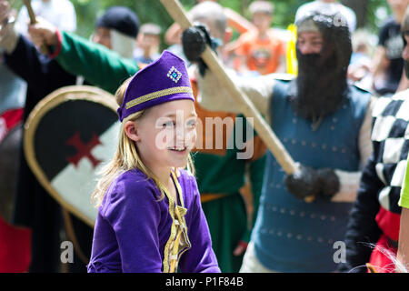 Nis, Serbia - June 10, 2018: Medieval little Princess in purple dress and knights with weapon in air in blurred background. Middle ages festival - Stock Photo
