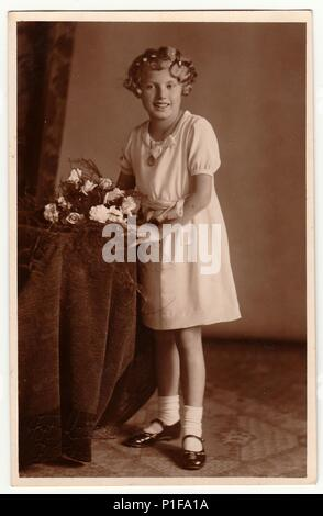 LIBEREC (REICHENBERG), THE CZECHOSLOVAK REPUBLIC - CIRCA 1930s: Vintage photo shows young girl with bouquet poses in a photography studio. Photo with dark sepia tint. Black & white studio portrait. - Stock Photo