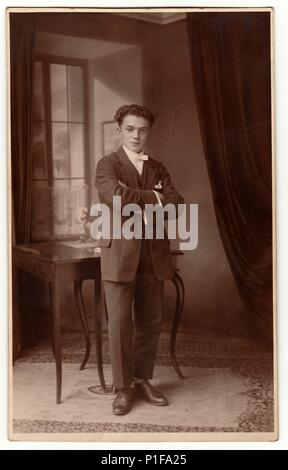 THE CZECHOSLOVAK REPUBLIC - CIRCA 1920s: Vintage photo shows young man poses in the room. Antique black & white studio portrait. - Stock Photo