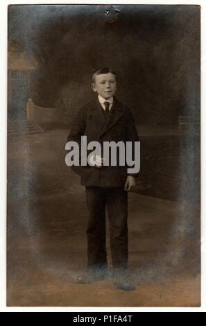 THE CZECHOSLOVAK REPUBLIC - CIRCA 1920s: Vintage photo shows boy wears suit and tie. Antique black & white photo taken outdoors. On top of the image is imprint of drawing pin. Photo has dark tint. - Stock Photo