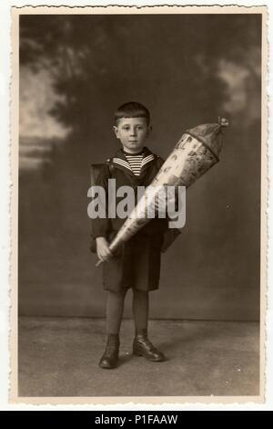EILENBURG, GERMANY - CIRCA 1920s: Vintage photo shows pupil boy with school cone. Studio photo with sepia tint. - Stock Photo