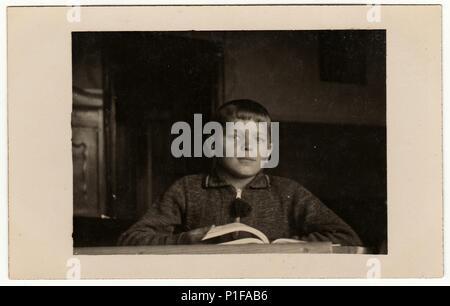 EILENBURG, GERMANY - CIRCA 1950s: Vintage photo shows pupil boy with book at the desk. Black & white retro photo. - Stock Photo