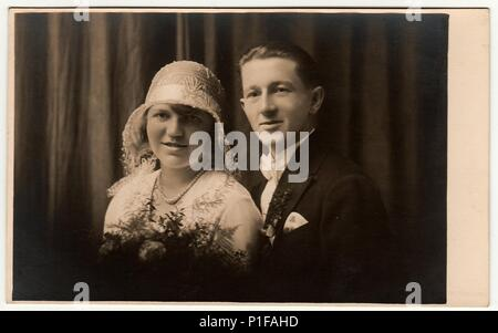 LIBEREC (REICHENBERG), THE CZECHOSLOVAK  REPUBLIC - CIRCA 1920s: Vintage photo of newlyweds. Bride wears white hat with lace (bobbin). Groom wears posh clothing, white bow-tie.  Black & white antique studio portrait. - Stock Photo