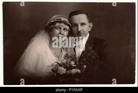 LIBEREC (REICHENBERG), THE CZECHOSLOVAK  REPUBLIC - CIRCA 1920s: Vintage photo of newlyweds with wedding bouquet. Bride wears wedding veil headdress. Groom wears posh clothing, white bow-tie. Black & white antique studio portrait. - Stock Photo