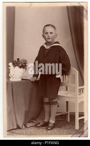 LEIPZIG, GERMANY - CIRCA 1930s: Vintage photo shows a young boy wears sailor costume. Black & white antique studio portrait. - Stock Photo