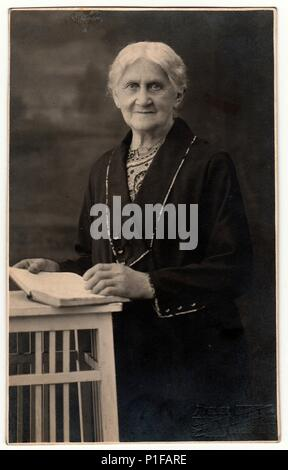 LIBEREC (REICHENBERG), THE CZECHOSLOVAK REPUBLIC - CIRCA 1920s: Vintage photo shows old woman with book poses in a photography studio. Photo with dark sepia tint. Black & white studio portrait. - Stock Photo