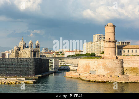 Saint Jean fort in Marseille under a stormy sky with the MuCEM and Villa Mediterranee buildings and Sainte Marie Majeure cathedral in the distance. - Stock Photo