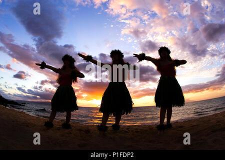 Three hula dancers at sunset at Palauea Beach, Maui, Hawaii. - Stock Photo