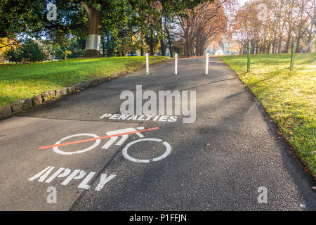 'Penalties Apply' warning sign painting on the asphalt footpath to remind cyclists to dismount in the public garden. Melbourne, VIC Australia