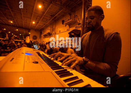 161028-N-WS581-074    ARABIAN GULF (Oct. 28, 2016) Petty Officer 2nd Class Gabriel Blake plays the piano during a Morale, Welfare and Recreation (MWR) Halloween event in the hangar bay of the aircraft carrier USS Dwight D. Eisenhower (CVN 69) (Ike). Ike and its Carrier Strike Group are deployed in support of Operation Inherent Resolve, maritime security operations and theater security cooperation efforts in the U.S. 5th Fleet area of operations. (U.S. Navy photo by Petty Officer 3rd Class Andrew J. Sneeringer) - Stock Photo