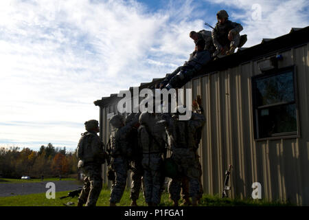 Soldiers from 94th Military Police Company work collectively to lower an person acting as an injured civilian from a rooftop during a training exercise at Fort Drum, NY, on October 23. The training focused on controlling a riot, treating injured civilians, and providing MEDEVAC services during 10th Mountain Division (LI)'s annual Mountain Peak exercise. (U.S. Army photo by Spc. Thomas Scaggs) Photo cropped, color and lighting balanced in Photoshop 161023-A-TZ475-361 - Stock Photo