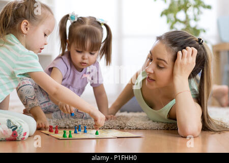 Happy family. Young mother playing ludo boardgame with her daughters while spending time together at home. - Stock Photo
