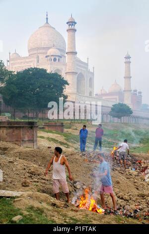 Local men burning garbage on the bank of Yamuna river near Taj Mahal, Agra, Uttar Pradesh, India. Taj Mahal was designated as a UNESCO World Heritage  - Stock Photo