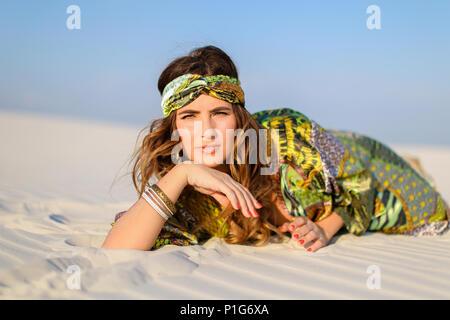 Young stylish woman wearing green beach robe lying on white sand - Stock Photo