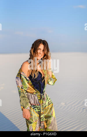 Young woman wearing green beach robe standing on white sand. - Stock Photo