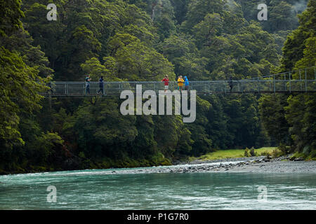 Tourists on footbridge over Makarora River, Blue Pools, Mount Aspiring National Park, Haast Pass, near Makarora, Otago, South Island, New Zealand - Stock Photo