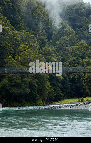 Tourists on footbridge over Makarora River, Blue Pools, Mount Aspiring National Park, Haast Pass, near Makarora, Otago, South Island, New Zealand (mod - Stock Photo