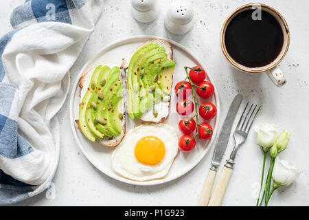 Breakfast avocado toast with fried egg, cherry tomatoes, cup of coffee and white flowers. Breakfast in bed. Healthy lifestyle, healthy eating concept - Stock Photo