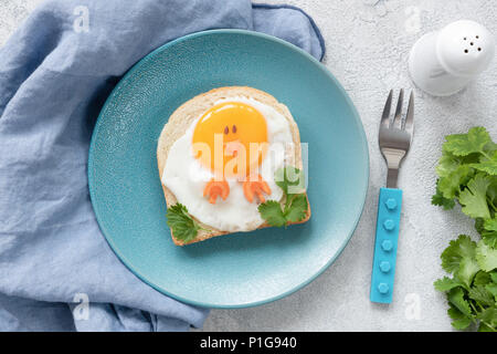 Creative food art breakfast idea for kids. Chicken shaped toast on a blue plate, meal for kids. Children breakfast, top view - Stock Photo