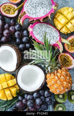 Exotic or tropical fruits assortment. Pineapple, coconut, passion fruit, pitaya, grapes and kiwi. Group of fresh fruits. Fruit background - Stock Photo