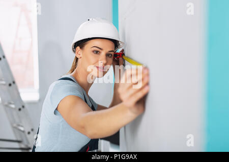 Serious female builder holding a measuring tape - Stock Photo