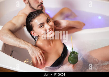 smiling Asian lady enjoying having tube with loving guy - Stock Photo