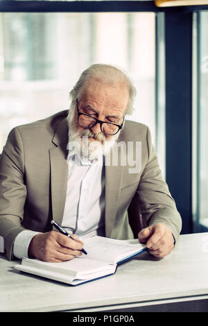 portrait of old man with grey hair and beard consentrated on his writing - Stock Photo