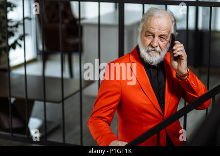 closeup portrait of senior chief talking on the phone and standing on the stair - Stock Photo
