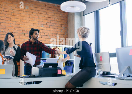Indian Man and Caucasian woman standing and shaking hands. - Stock Photo