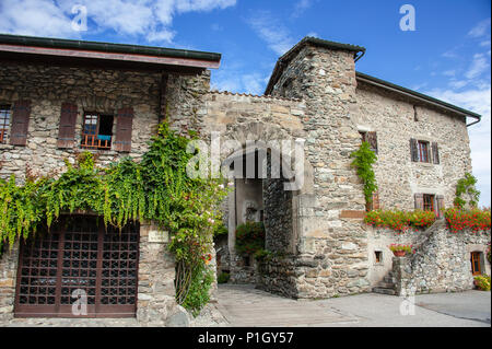 Yvoire, (Pearl of Lake Geneva) market square. Ancient archway, medieval architecture, fortified old town walls and floral display against blue sky - Stock Photo