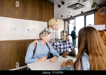 attractive female boss standing between her male workers - Stock Photo