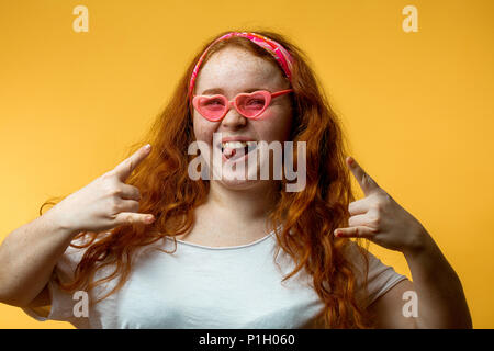 Portrait of beautiful smiling redhead girl wearing big fashion pink glasses - Stock Photo