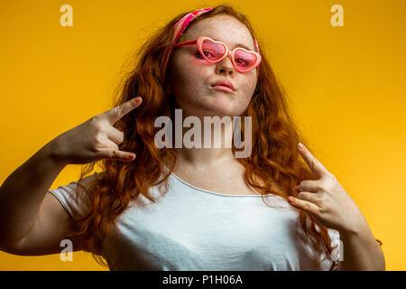 Portrait of beautiful smiling redhead girl wearing big pink glasses - Stock Photo
