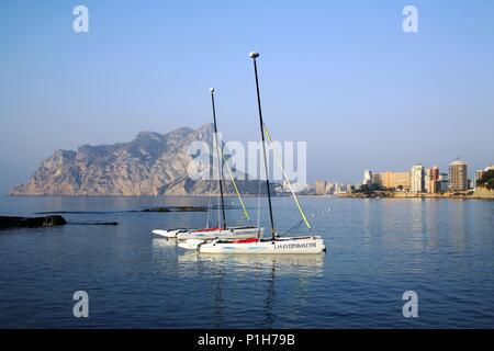 SPAIN - Valencia autonomous region - Marina Alta (district) - Alicante. Calpe / Calp; playa de Levante o de la Fosa y Peñon de Ifach vista desde la Cala de Les Bassetes (con puerto de actividades deportivas). - Stock Photo
