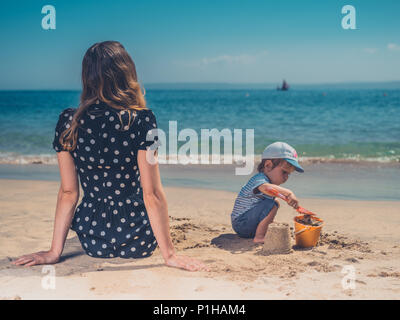 A young mother is playing with her son on the beach, building sand castles - Stock Photo