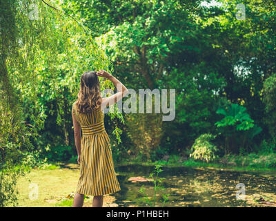 A fashionable woman wearing a dress is standing by a pond in a garden - Stock Photo
