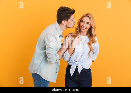 Image of young people wearing denim clothing in relationship expressing love and affection while man kissing woman on cheek isolated over yellow backg - Stock Photo