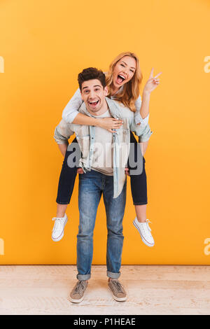Full length photo of young couple having fun while guy giving piggyback ride to lovely girl showing peace sign isolated over yellow background - Stock Photo
