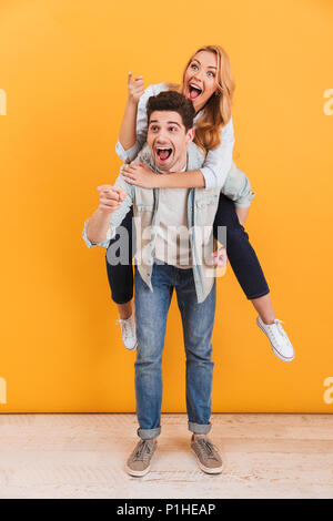 Full length image of caucasian couple having fun and pointing fingers at copyspace while man piggybacking joyful woman isolated over yellow background - Stock Photo