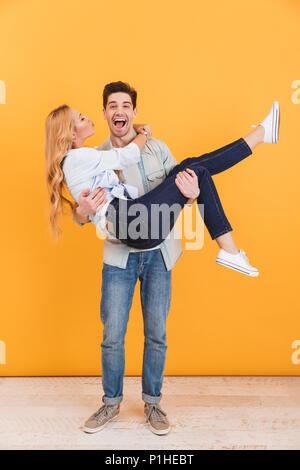 Full length photo of cheerful man smiling and holding woman in his arms who kissing his cheek isolated over yellow background - Stock Photo