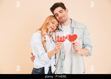 Portrait of joyful romantic people man and woman in basic clothing holding red paper hearts on sticks and hugging with closed eyes isolated over beige - Stock Photo