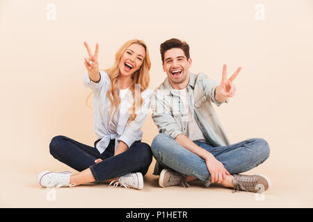 Image of happy two friends man and woman in casual clothing sitting on the floor with legs crossed and showing victory sign isolated over beige backgr - Stock Photo