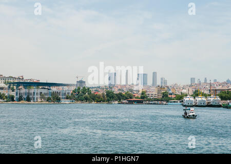 View of the European part of Istanbul from the waters of the Bosphorus. Ships and boats float on the water and stand in the port - Stock Photo