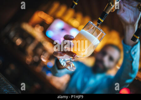 Barmen or brewer filling glass with beer. Barmen is pouring lager beer to glass from  beer taps. Bar or night club interior. - Stock Photo