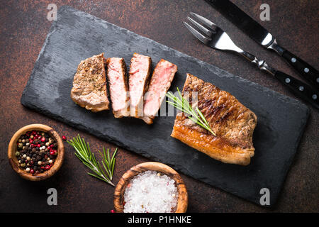 Beef steak. Grilled striploin steak on cutting board with nerbs and spices. Top view. - Stock Photo