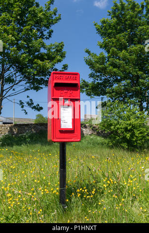 Red post box in a rural situation, North Yorkshire, UK. - Stock Photo