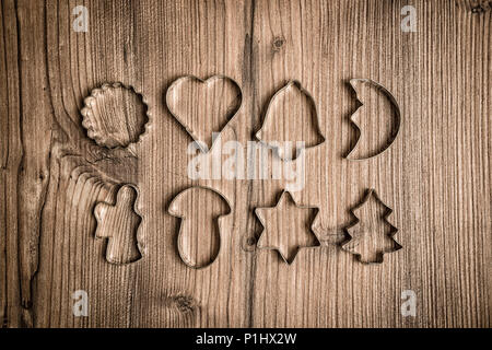 Set of traditional Christmas cookie cutters on textured wooden background, various shapes assorted - Stock Photo