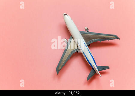 Simply flat lay design with miniature toy model plane pink pastel colorful trendy paper background. Travel by plane vacation summer weekend sea advent - Stock Photo