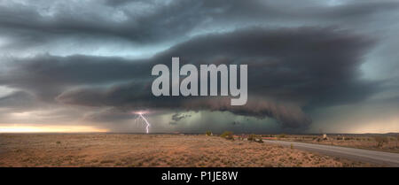 Cloud-to-ground lightning from a thunderstorm with shelfcloud above the New Mexican desert near Artesia (Eddy County) at sunset, USA - Stock Photo