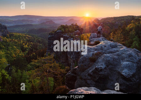 Photographer on the Heringsstein at sunrise, Elbe Sandstone Mountains, Saxony, Germany - Stock Photo